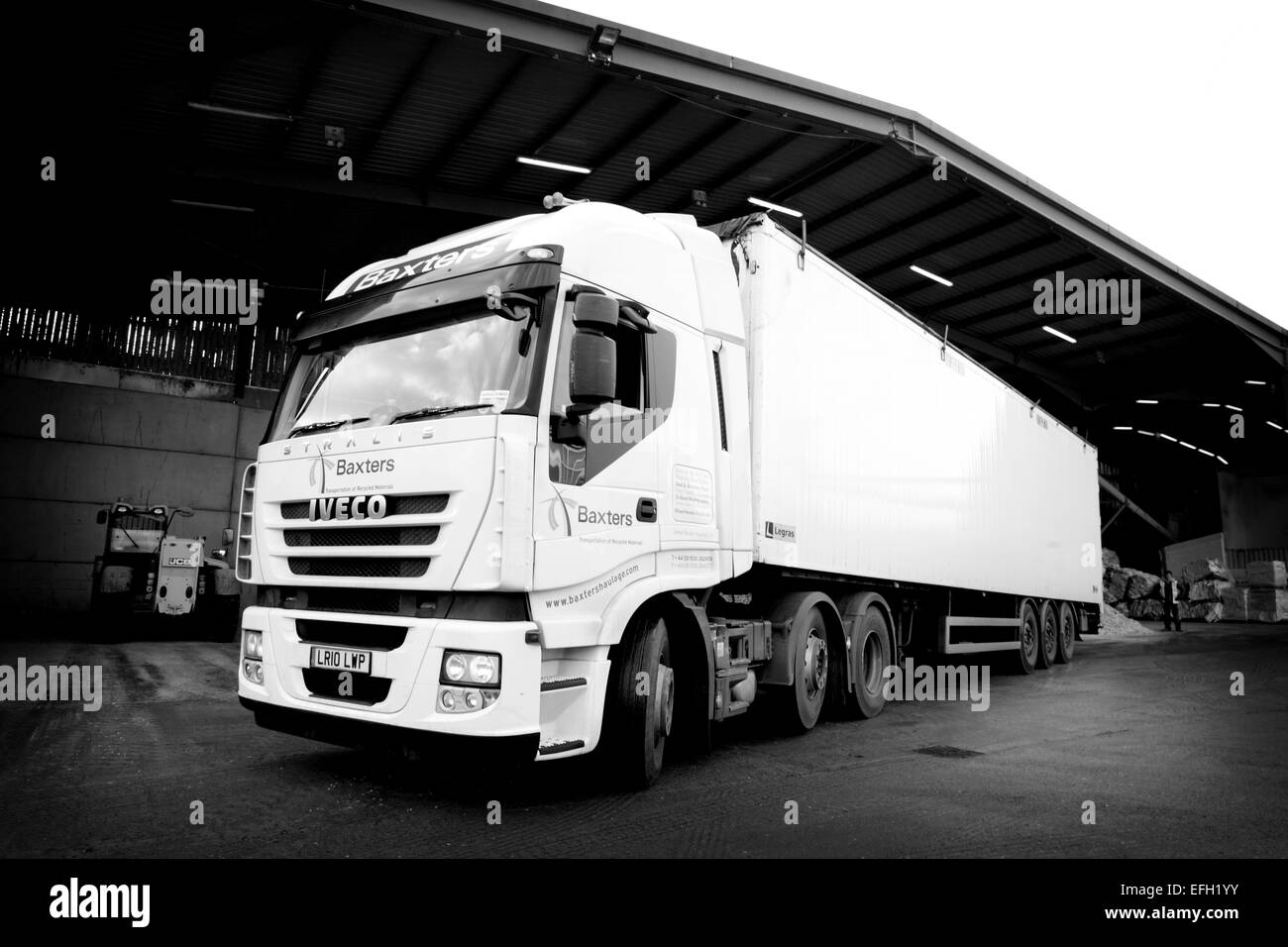 White lorry parked in loading bay at biomass plant, black and white - Stock Image