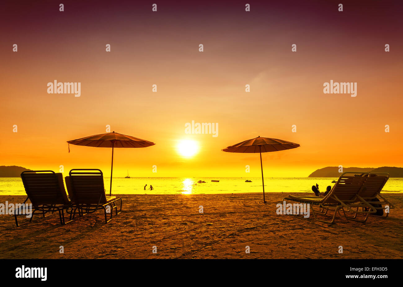 Retro filtered picture of beach chairs and umbrellas on sand at sunset. Concept for rest, relaxation, holidays. - Stock Image