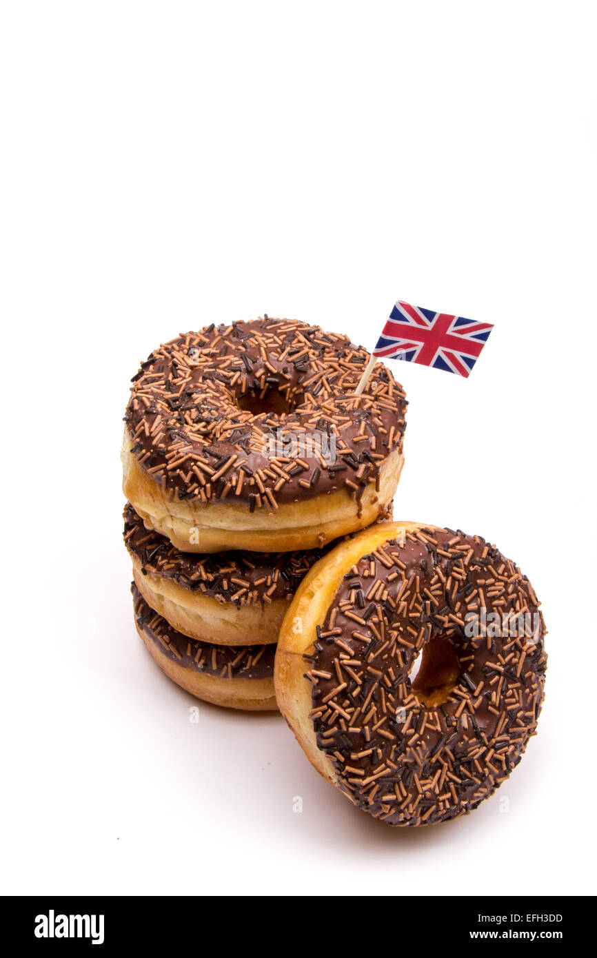 A pile of chocolate iced ring donuts on a white background with British Union Jack Flag - Stock Image
