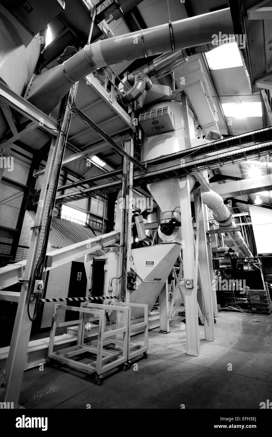 Industrial machinery and piping for production of biomass fuel, black & white - Stock Image