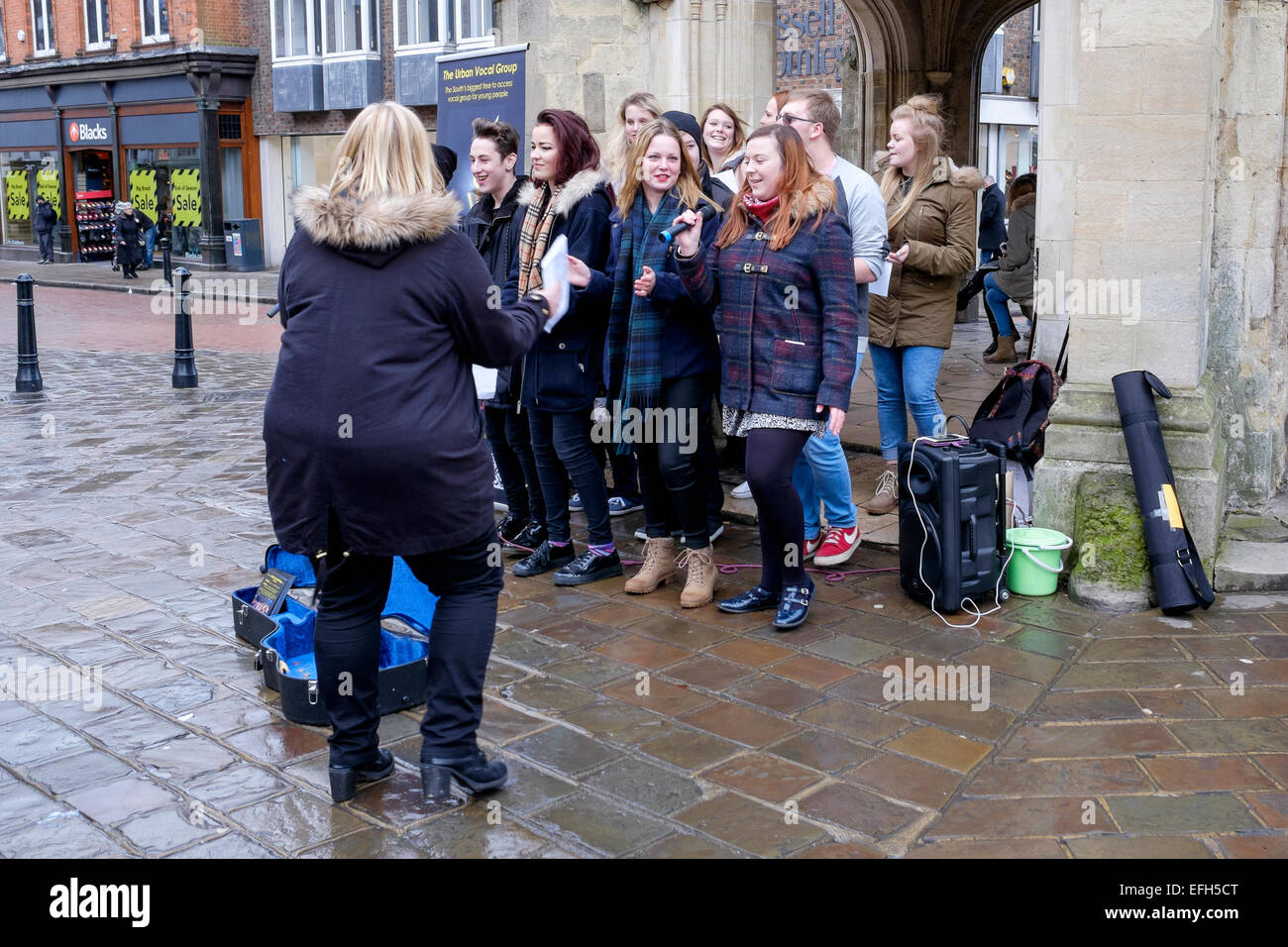 group of young people  singing and entertaining the public at the market cross in the centre of chichester west - Stock Image