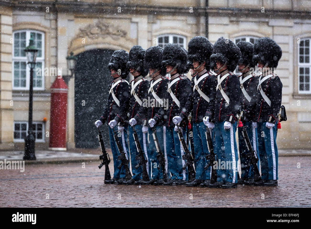 Royal Life Guards in front of Amalienborg Palace on a snowy day, Copenhagen, Denmark - Stock Image