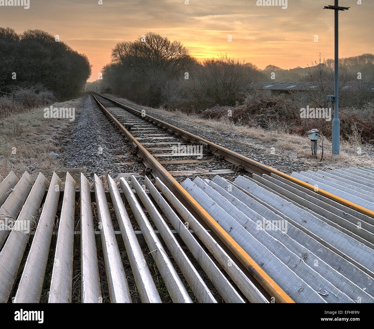 looking down an old rail track with sunrise - Stock Image