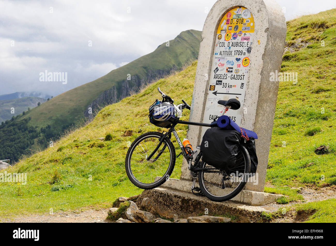 A sign post on Col d'Aubisque (1709m), Pyrenees, (France) with a bicycle leaning. Stock Photo