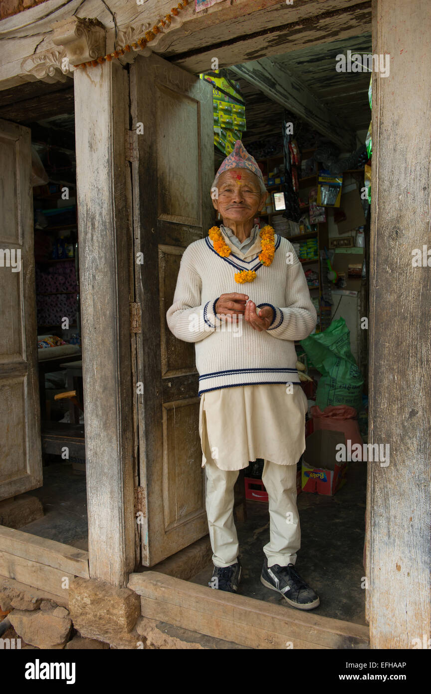 Old Newari man in a traditional Newari hat, standing in his shophouse, Nuwakot, Nepal - Stock Image