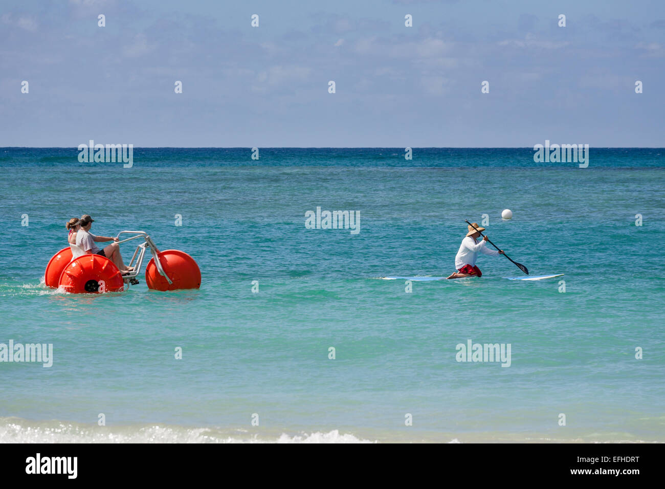 Old and New: water tricycle chases a kneeling surf board paddler. A couple peddle an orange water tricycle in hot - Stock Image