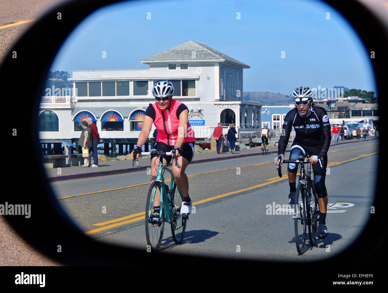 two cyclists  reflected in the rear view mirror ride into Sausalito from San Francisco - Stock Image