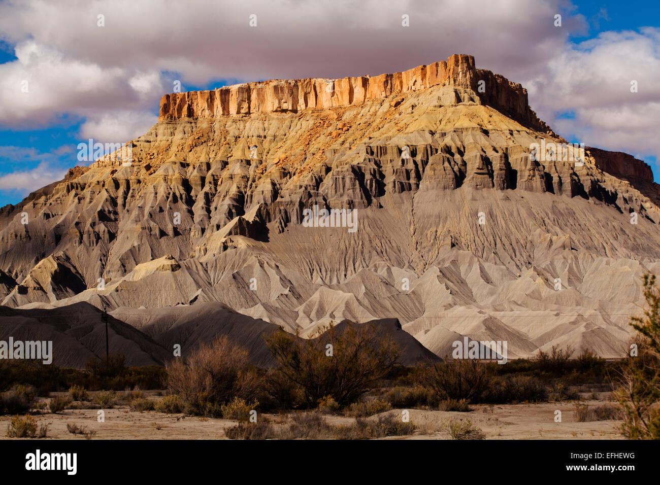 Sandstone butte layered over shale, near Capitol Reef National Park, Hanksville, Utah - Stock Image
