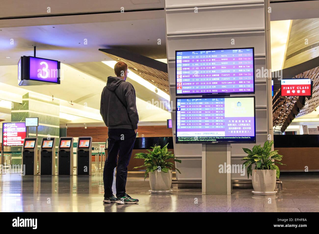 Taipei, Taiwan - January 9, 2015: Man stading in front of a Flight Information Board inside the Taiwan Taoyuan International - Stock Image
