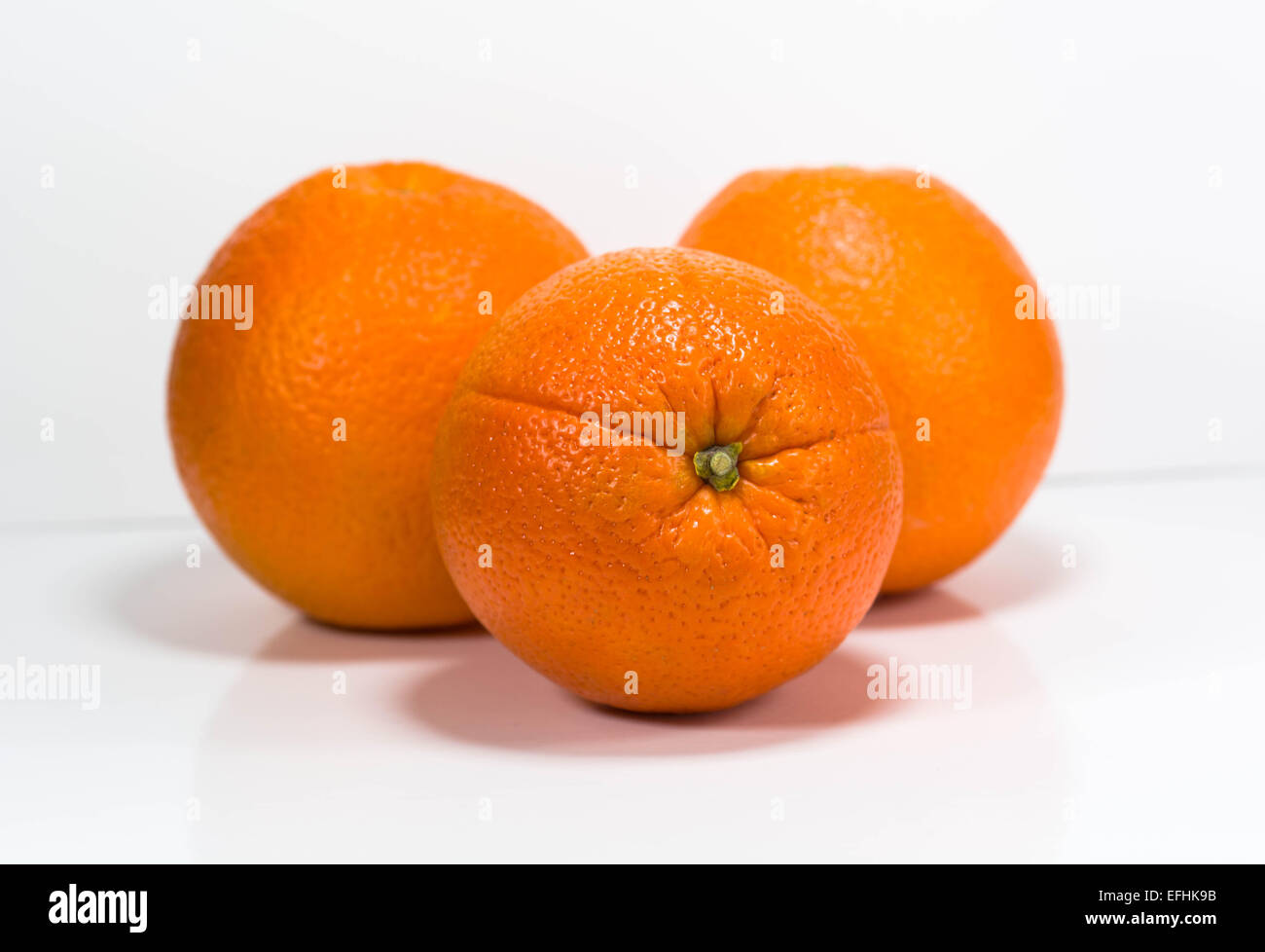 Three oranges isolated on a white background. - Stock Image