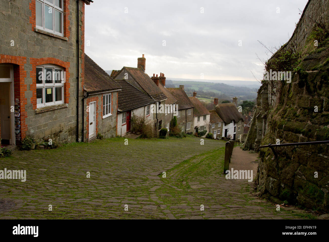 View at the top of Gold Hill, famous cobbled street in Shaftesbury, Dorset, England, looking downhill and to countryside - Stock Image