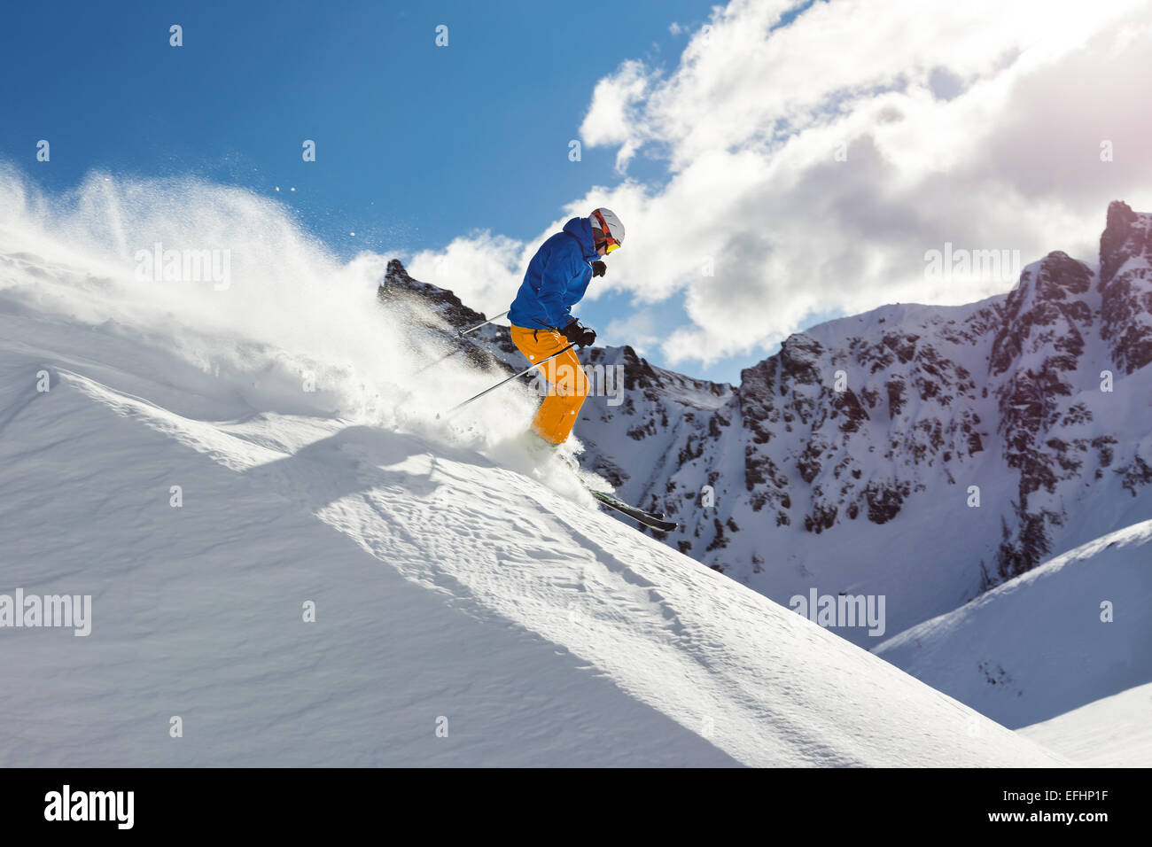 Male skier on downhill freeride with sun and mountain view - Stock Image
