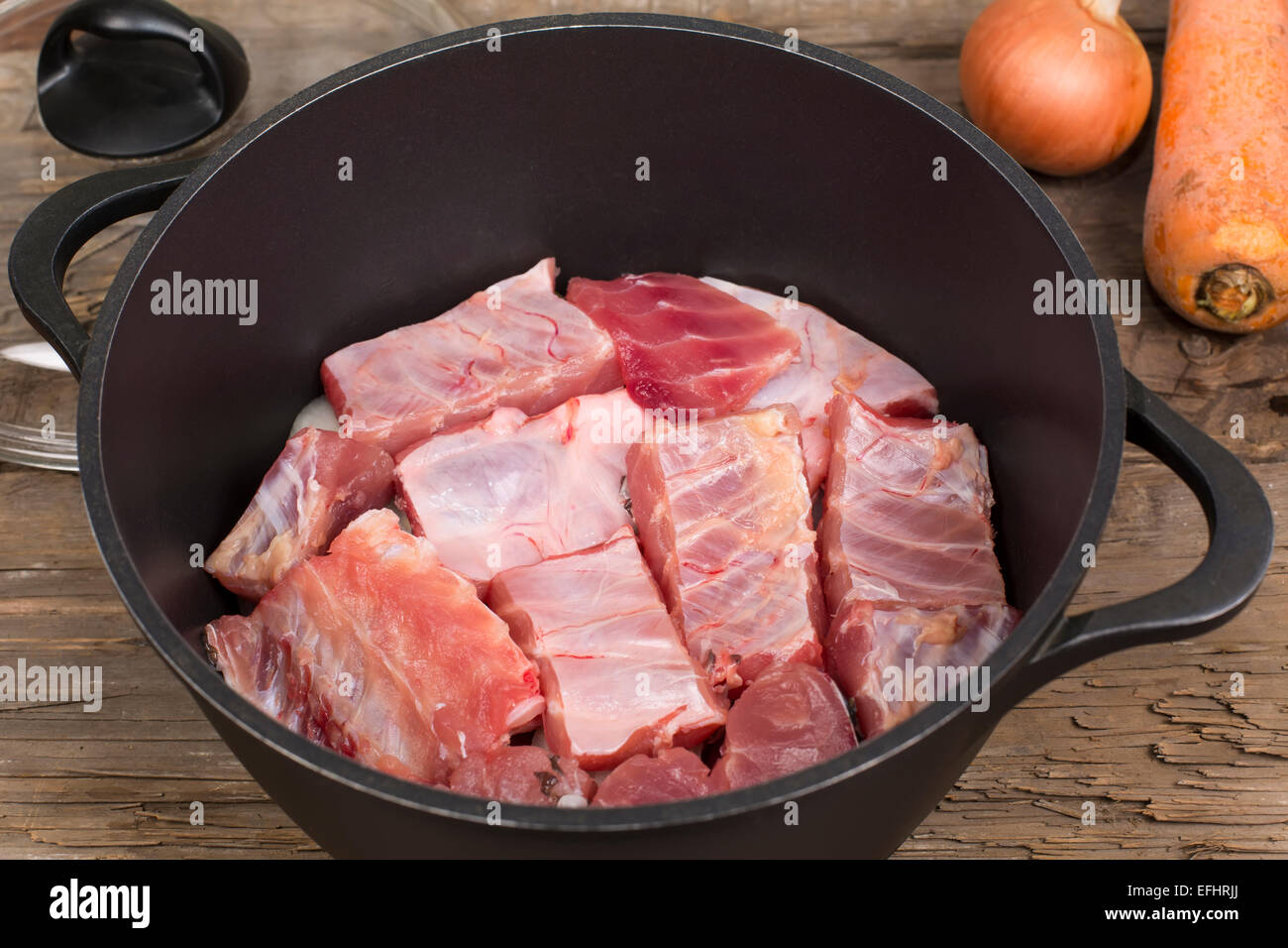 fish pieces in the pan prepared to extinguish with vegetables - Stock Image