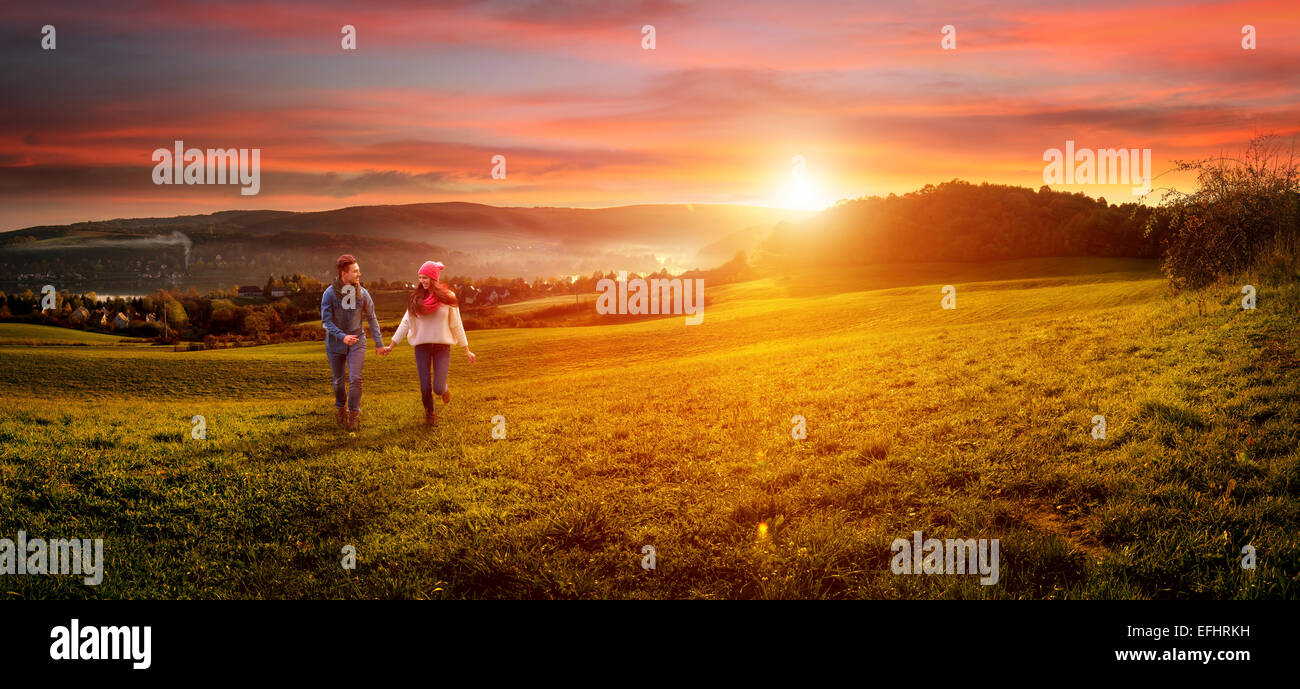Loving couple holding hands running on the field. beautiful landscape - Stock Image