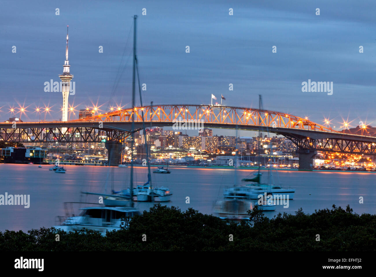 Auckland Harbour Bridge and skyline in the evening, harbour with sailing boats, Auckland, North Island, New Zealand - Stock Image