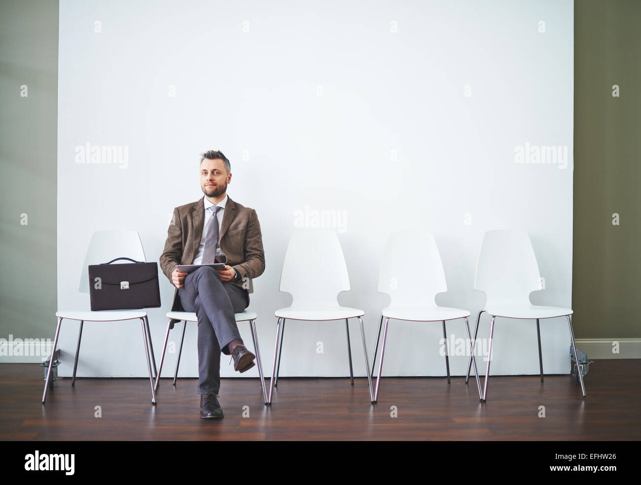 Confident man in formalwear waiting for his turn for interview - Stock Image
