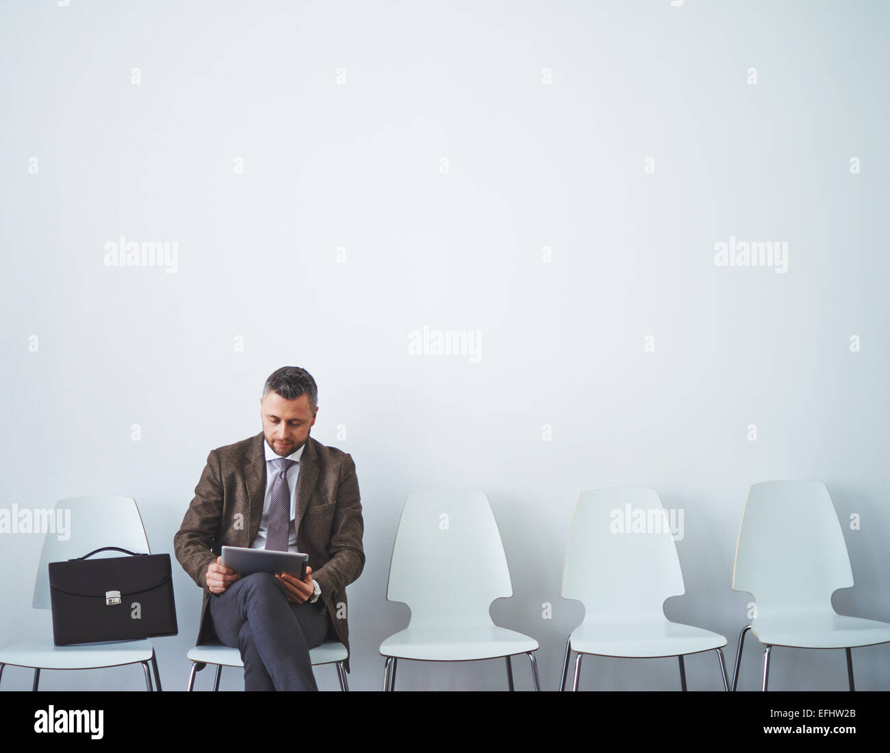 Mature man in formalwear networking before interview - Stock Image