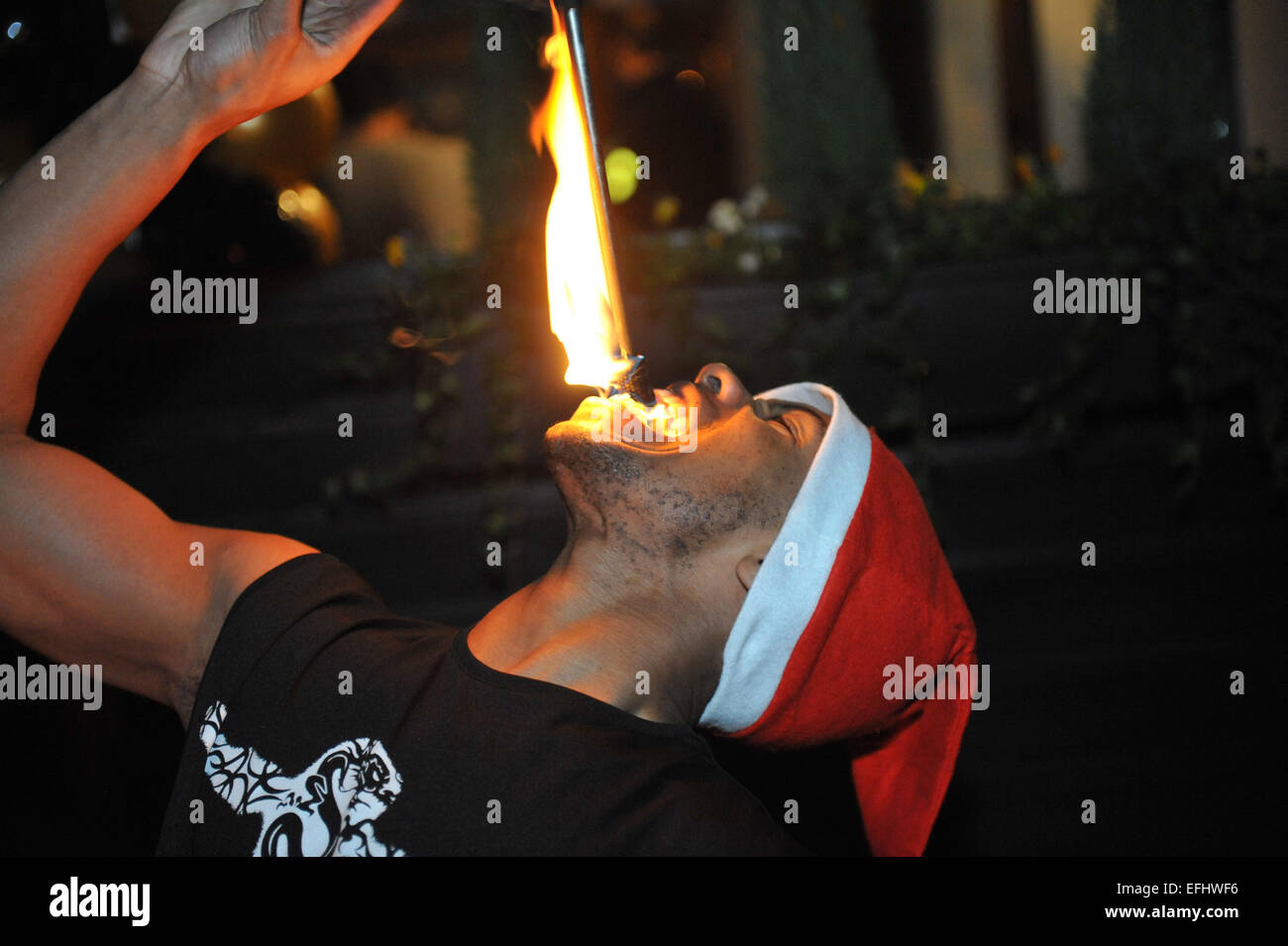 Fire eater entertainment at an opening party night. - Stock Image