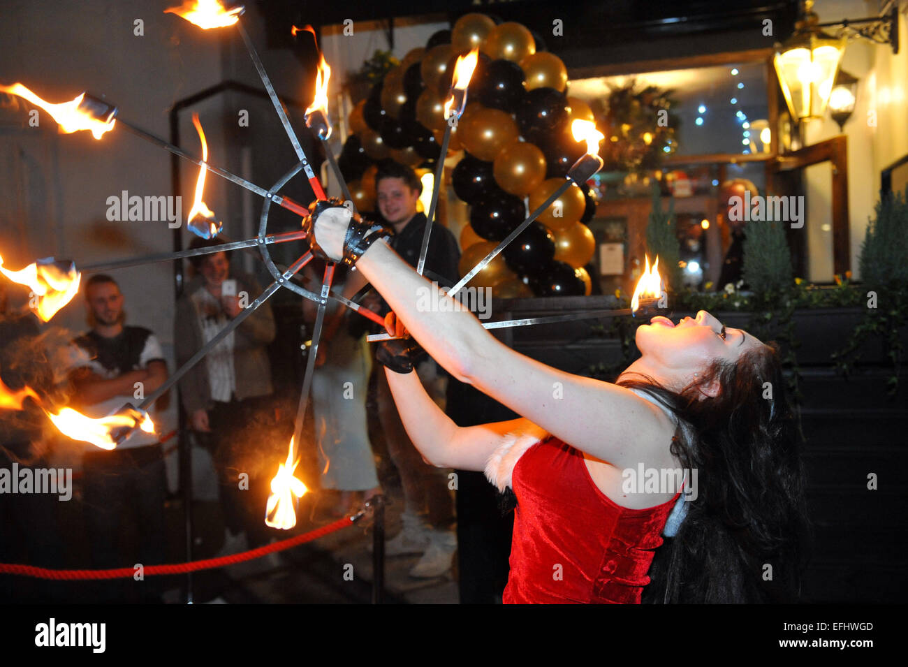 Female Fire eater entertains a crowd outside a pub at an opening party night. - Stock Image