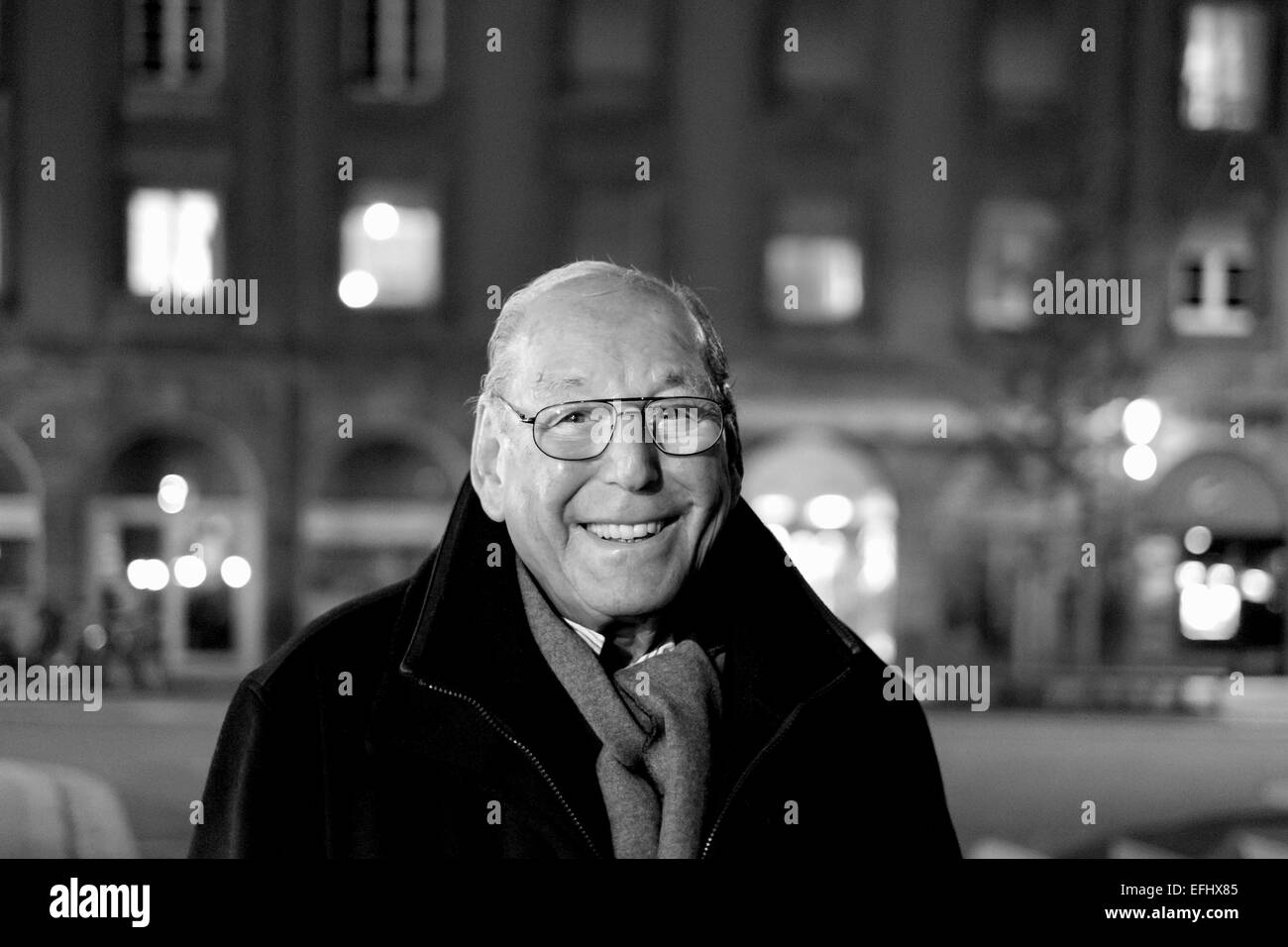 Black and white portrait of a smiling elderly man 80s at night - Stock Image