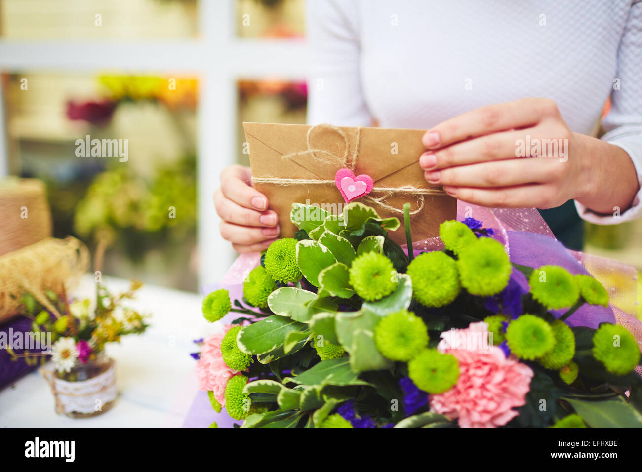 Female hands with love message putting it in floral bouquet - Stock Image