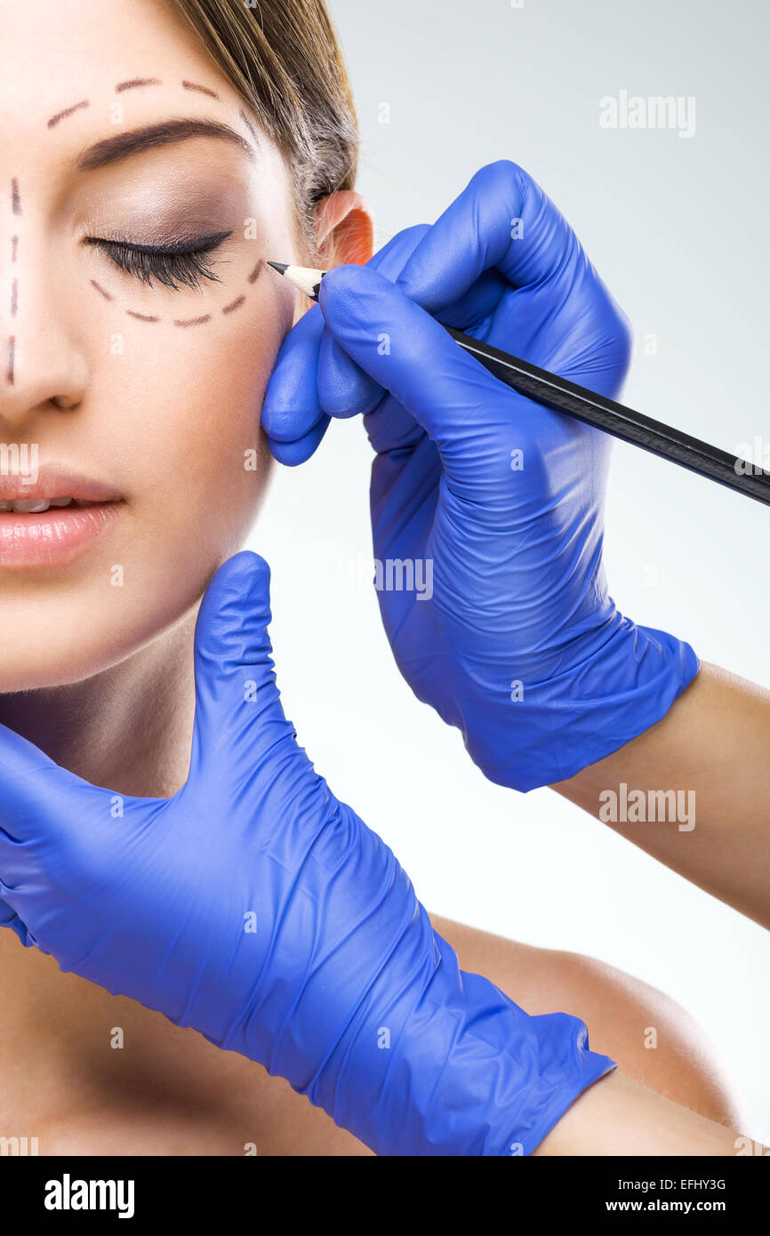 Beautiful woman half face photo plastic surgery, plastic surgeon hands - Stock Image