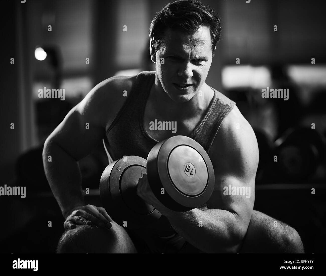 Young man doing exercise with barbell in gym - Stock Image