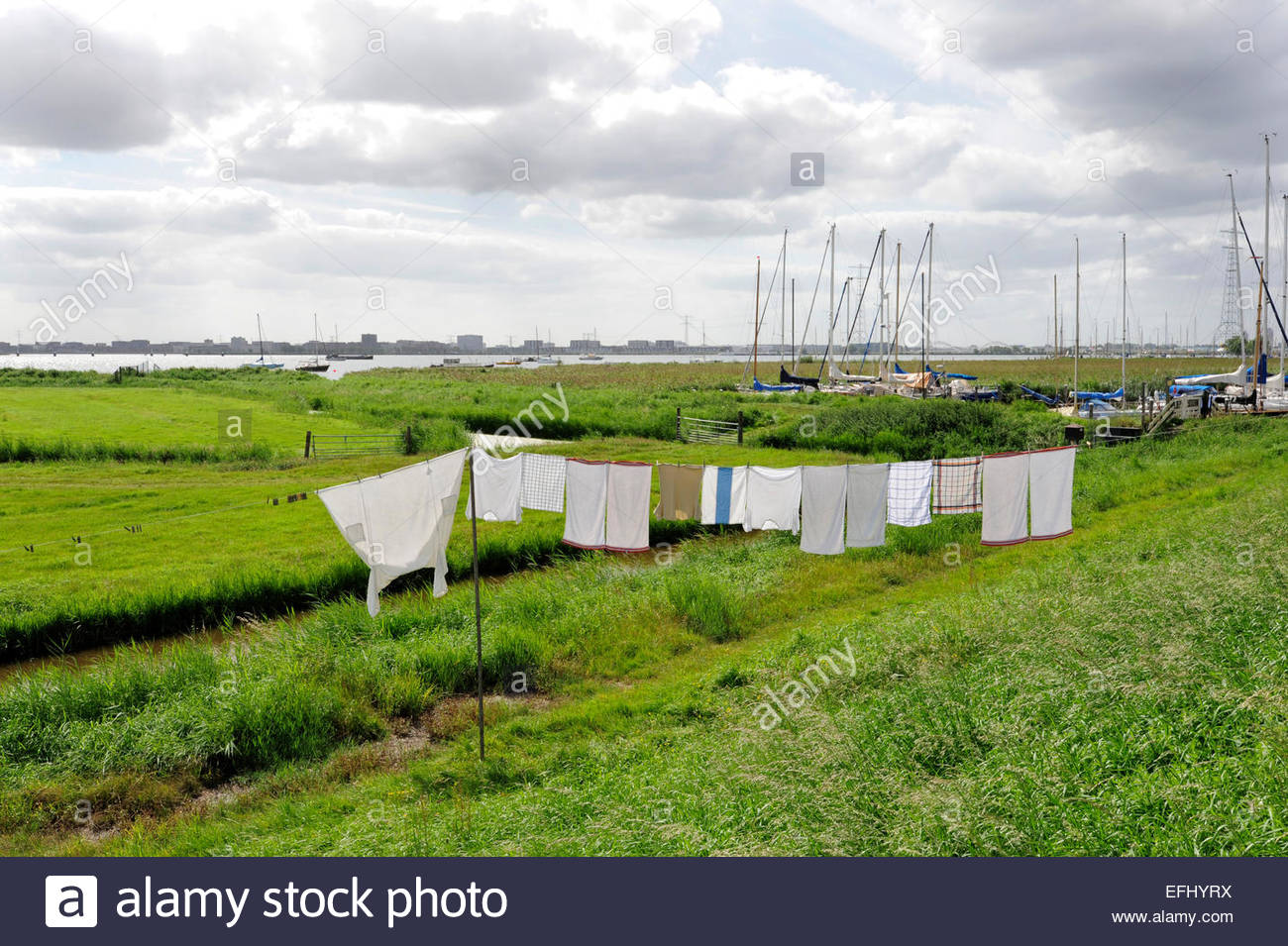 Clothesline on the embankment of the dyke to IJmeer lake, Durgerdam, Amsterdam, Holland, the Netherlands - Stock Image