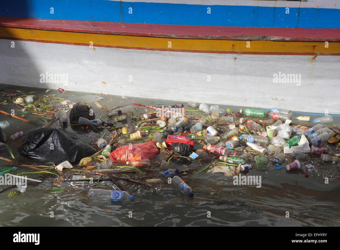 Plastic bottles and other trash floating in Manado River next to wooden boat - Stock Image