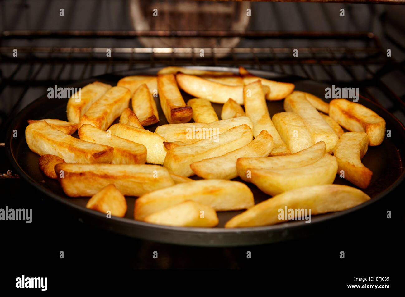 cooking oven chips in the oven - Stock Image