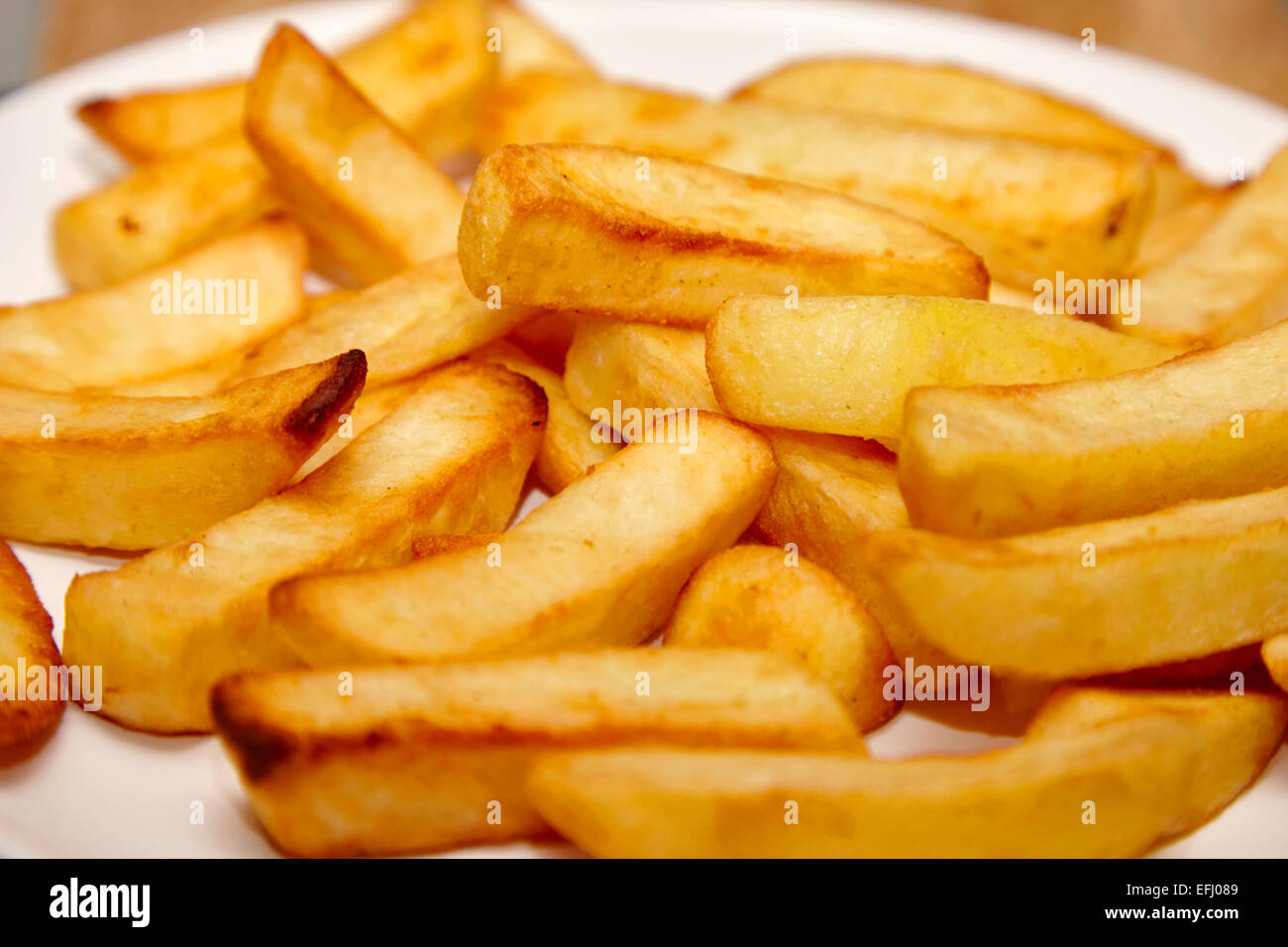 plate of cooked oven chips - Stock Image