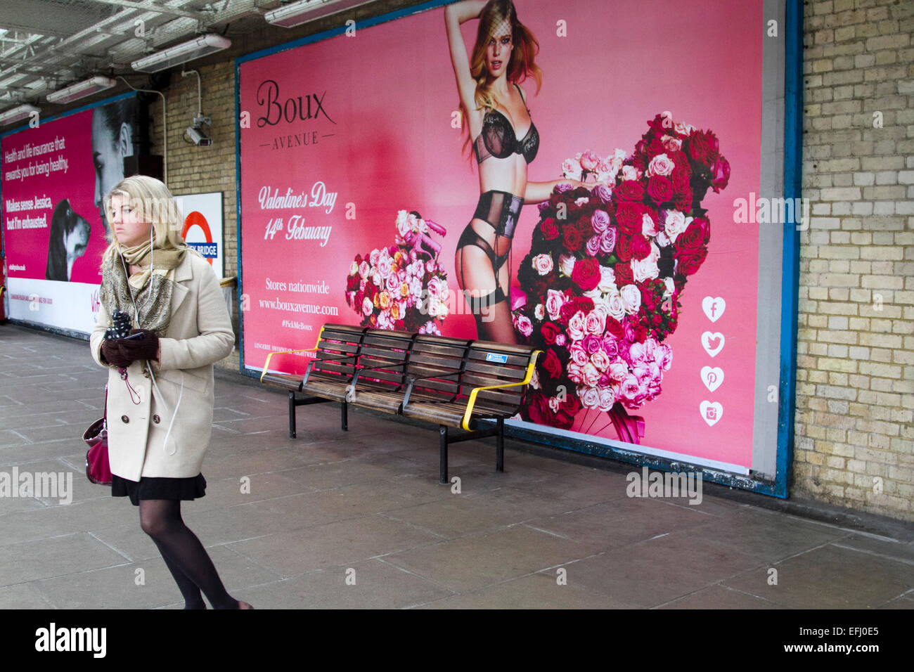 London, UK. 5th February, 2015. A commuter stands on  the platform at  Putney Bridge Station in front of a giant Stock Photo