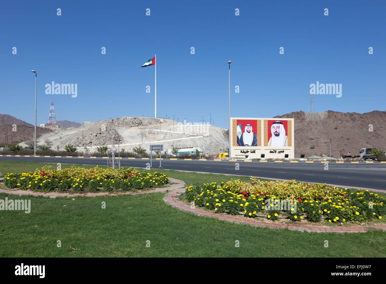 Roundabout in Fujairah with national flag and portraits of the rulers of the UAE - Stock Image
