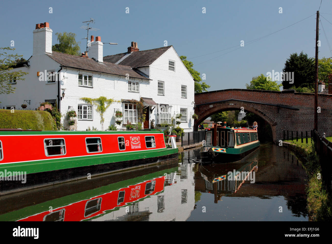 Narrowboats on the Bridgewater Canal by Lymm Bridge and Bridgewater House at Lymm in Cheshire - Stock Image