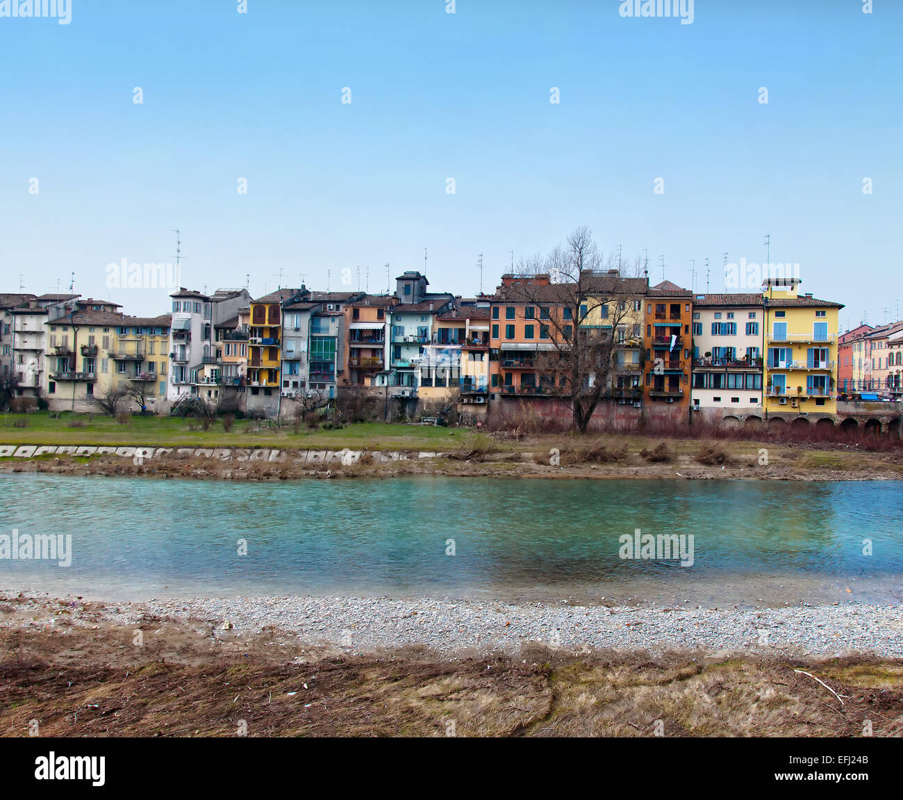 Parma river with typical city houses and bridge in winter day - Stock Image