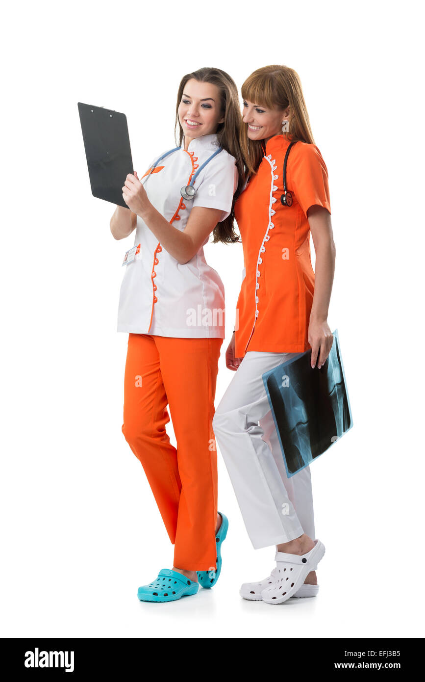 2 pretty nurse looking at the x-ray findings - Stock Image