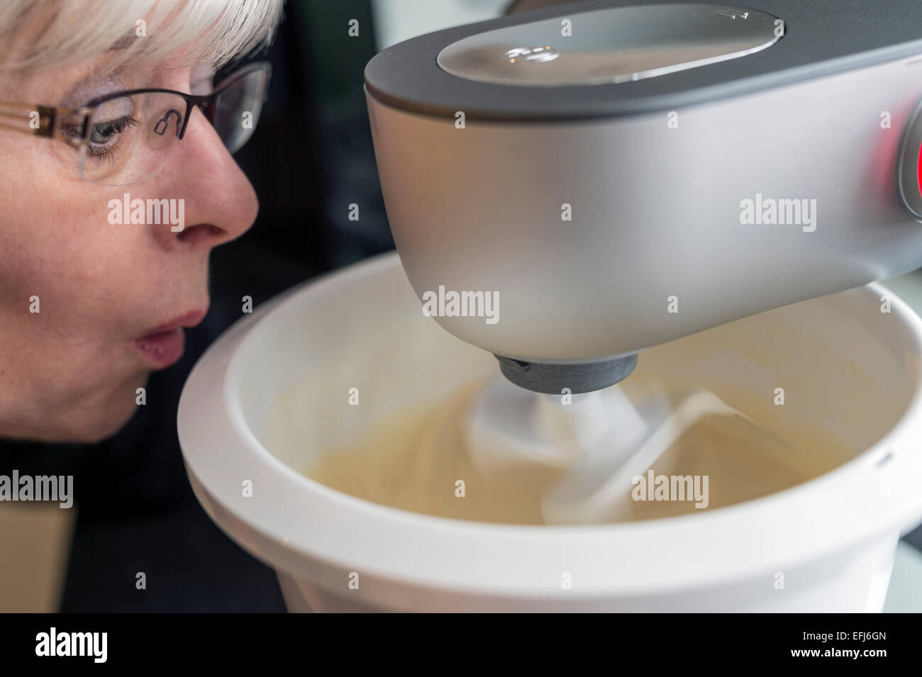 A wide-eyed woman looking at her kitchen machine, Germany - Stock Image
