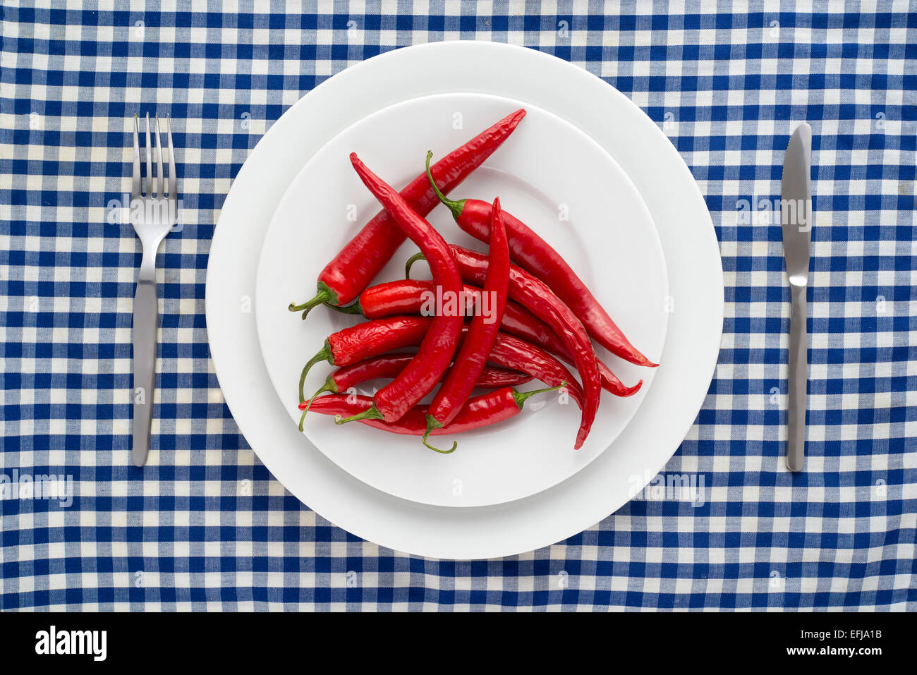 Red Chilli Peppers On A Checkered Tablecloth   Stock Image