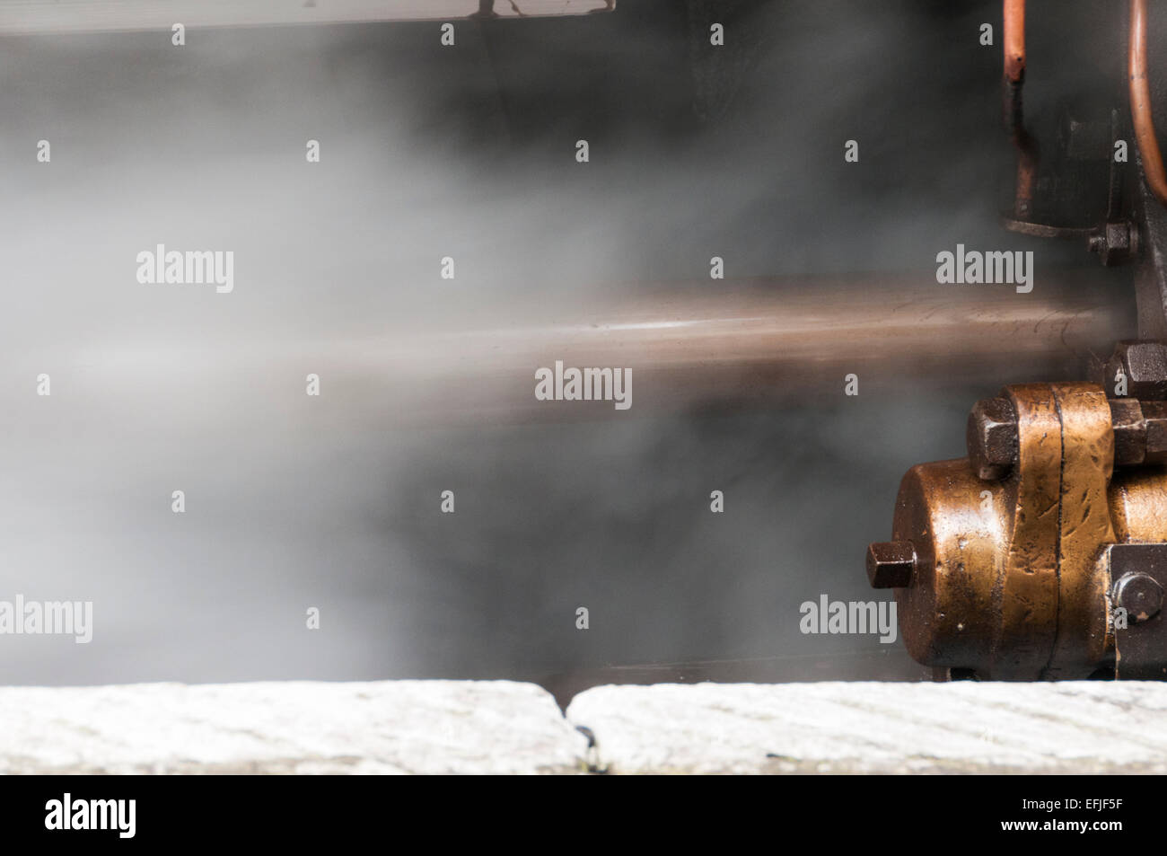 Close view of steam escaping from a piston that forms part of the driving mechanism of a steam loco - Stock Image