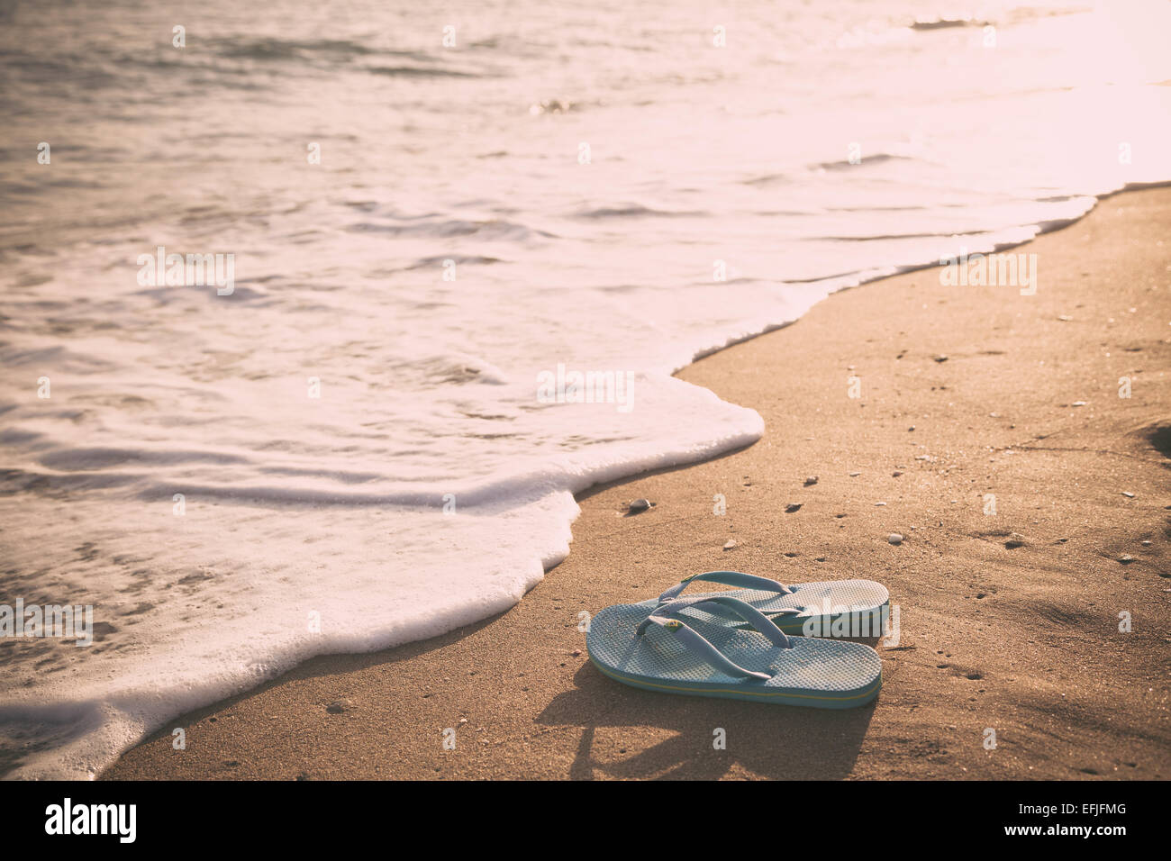 flip-flops, sandals sitting on the beach - Stock Image