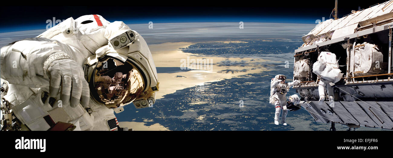 A team of astronauts performing work on a space station while orbiting over Earth. The Balitc region appears below - Stock Image