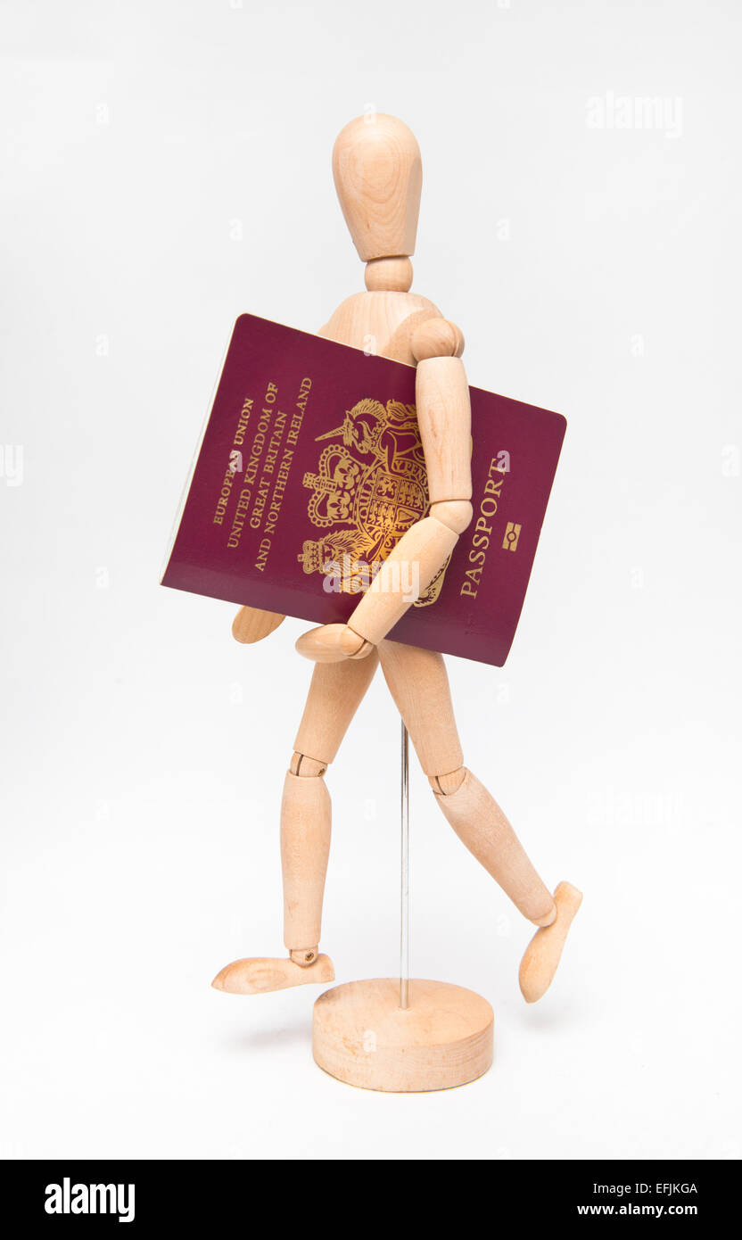 An artist's dummy holding a UK passport against a white background - Stock Image