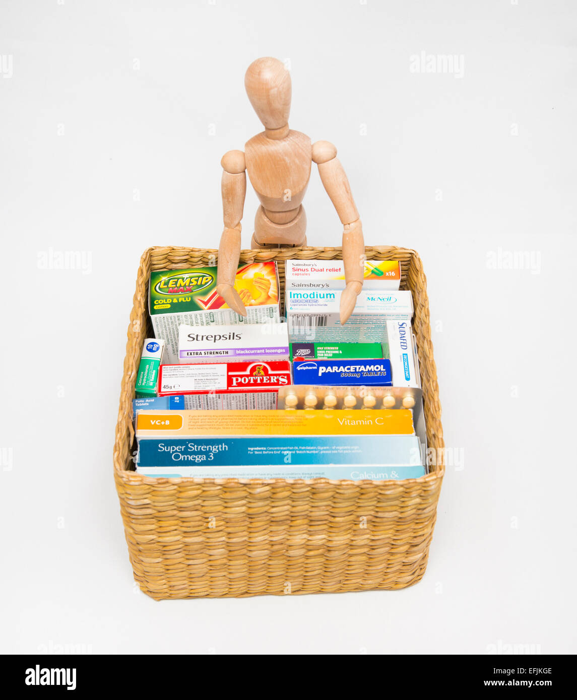 An artist's dummy and a basket of vitamins, remedies and medicine. - Stock Image