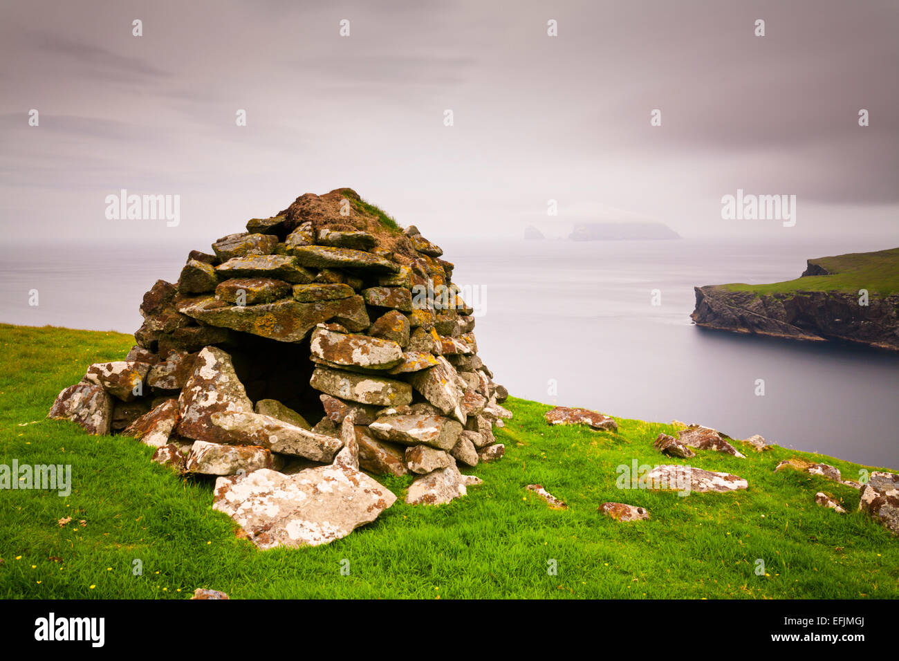 Cleit on Hirta with Boreray covered by clouds visible in the distance. Cleits were used by the St Kildans to store - Stock Image