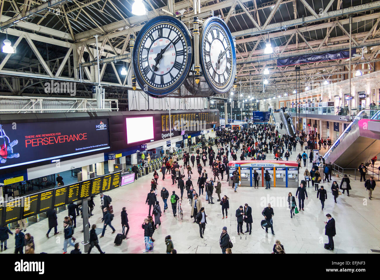 London Waterloo Station clock and concourse, crowded with early evening rush hour commuters by the sign boards under - Stock Image