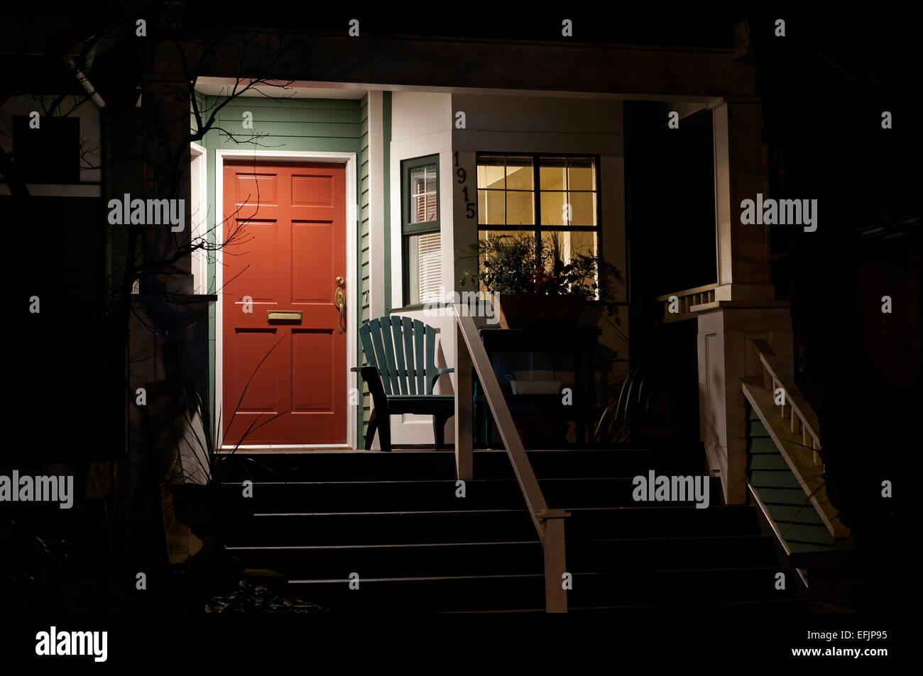 Front porch of a house and red wooden door at night - Stock Image