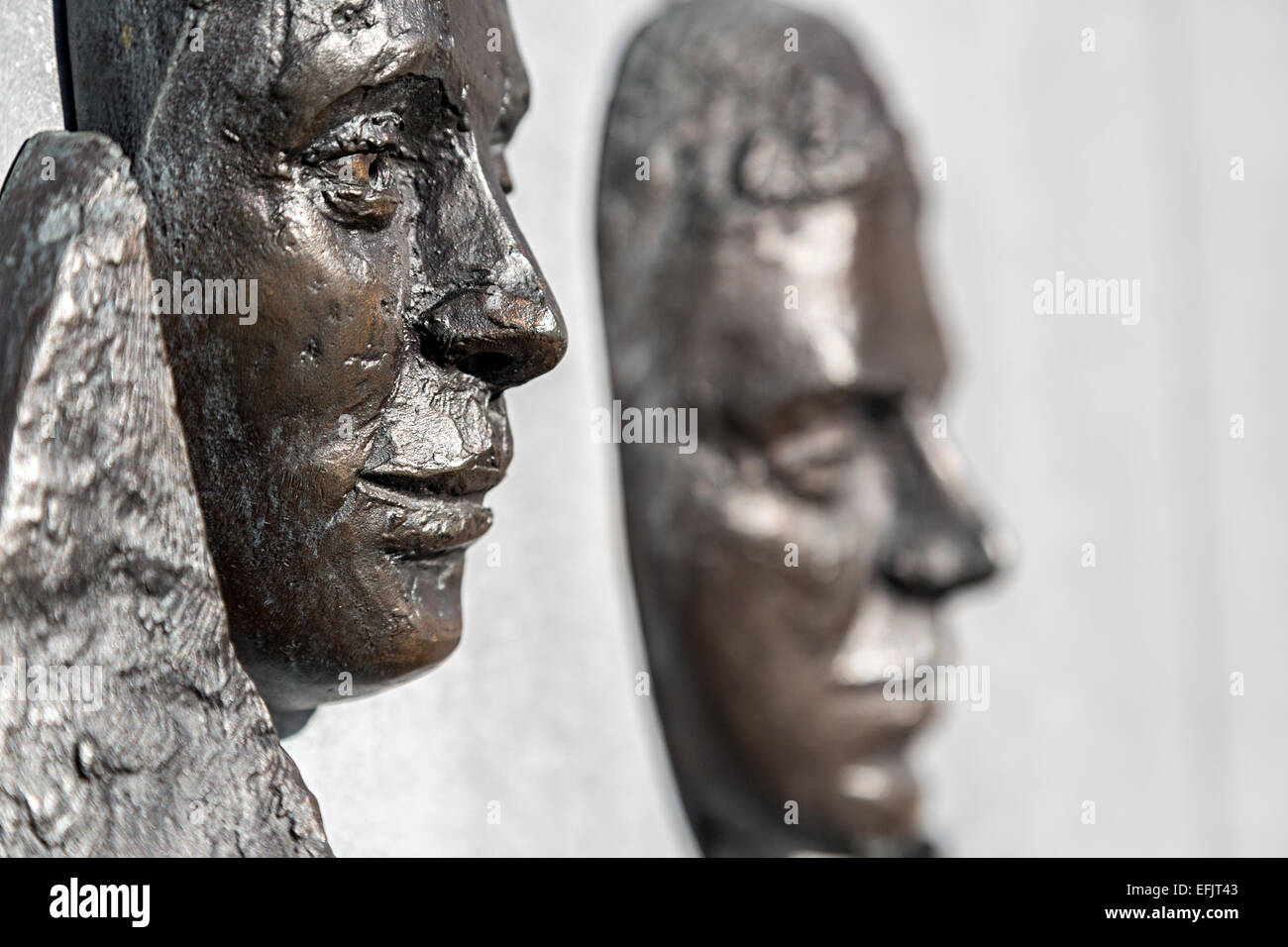 Faces in bronze on the John F. Kennedy memorial on quayside at New Ross, Co. Wexford, Republic of Ireland - Stock Image