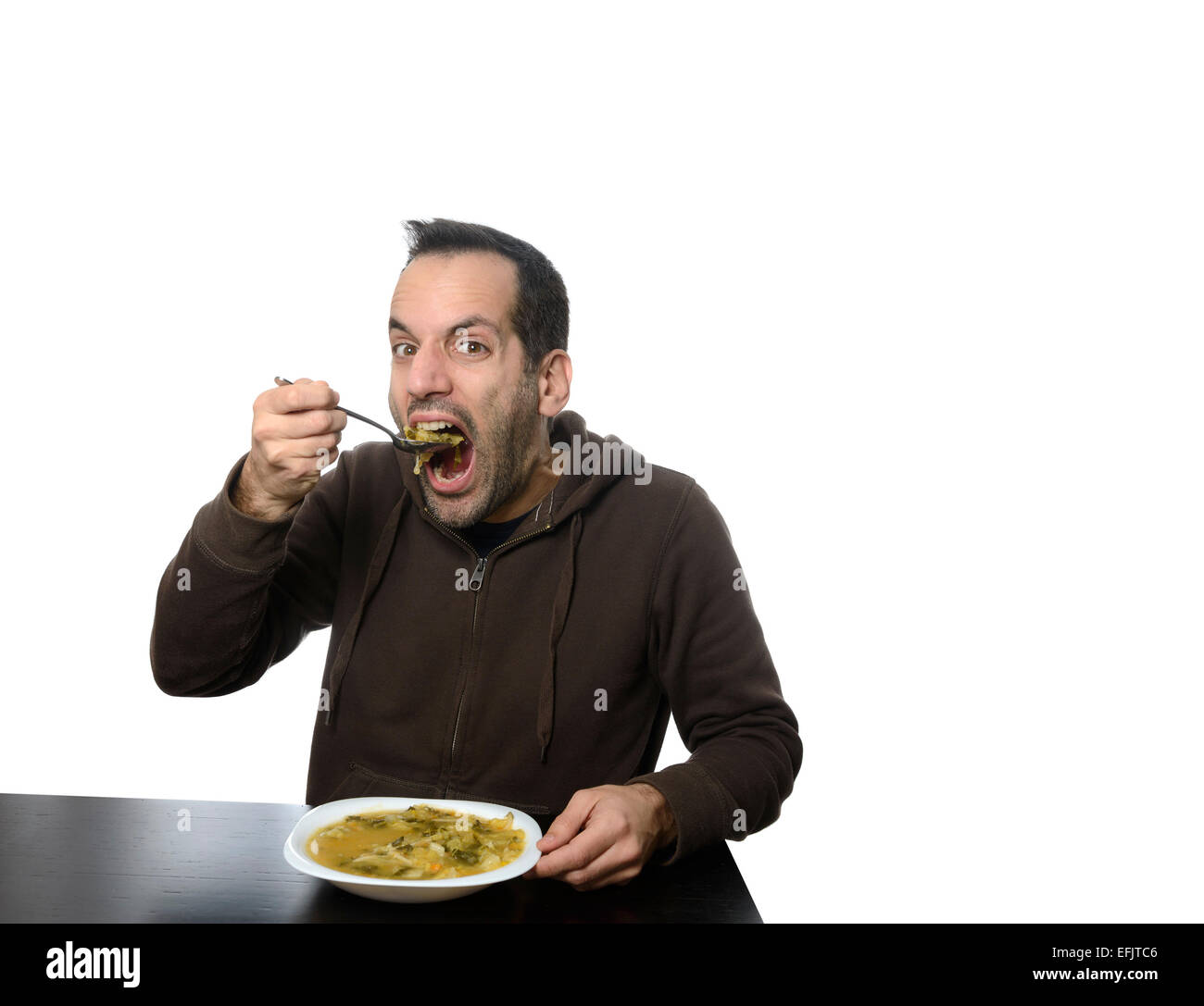Young man eating vegetable soup with his mouth wide open - Stock Image