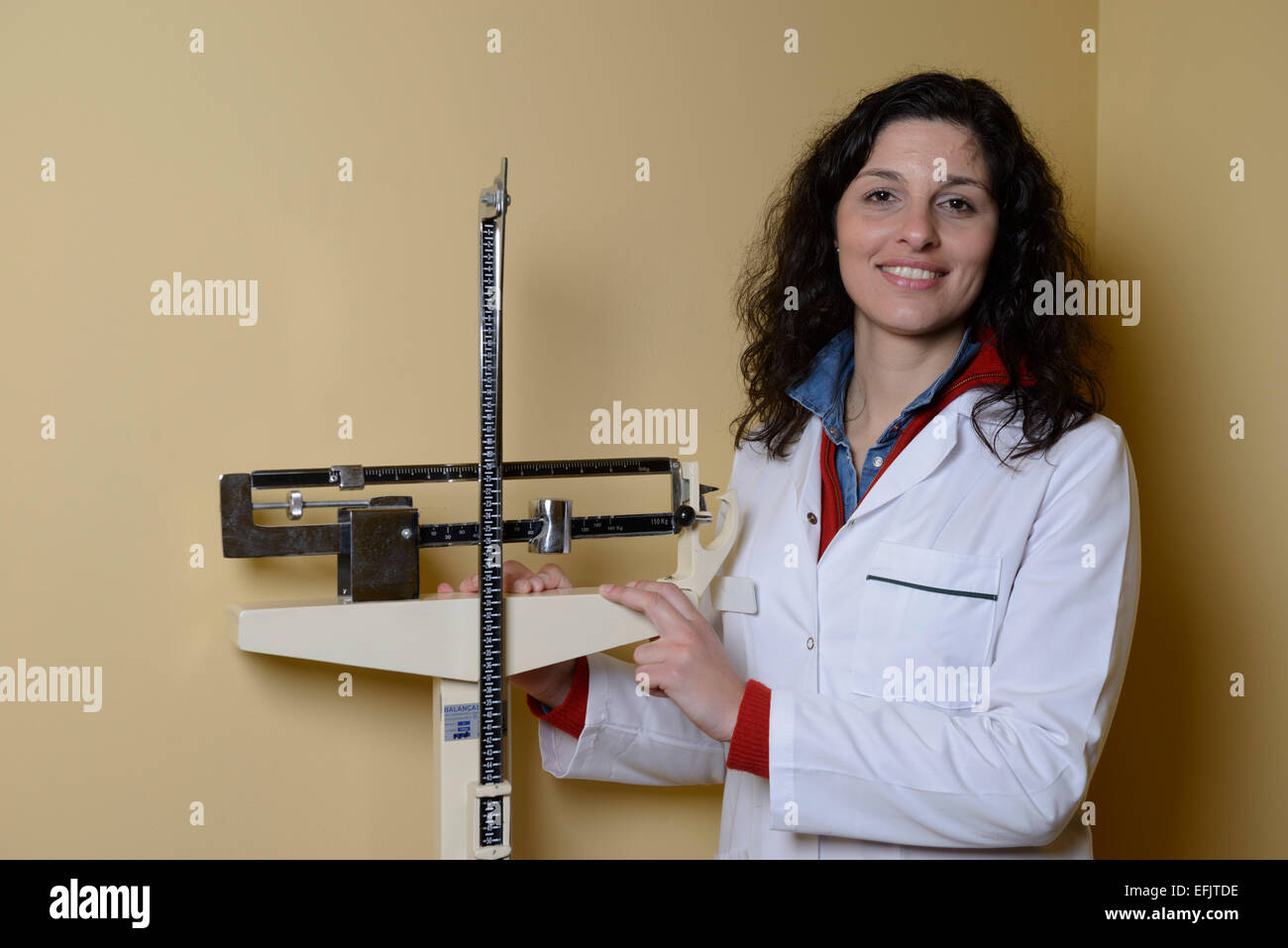 Portrait of a nutritionist next to weighing scales - Stock Image