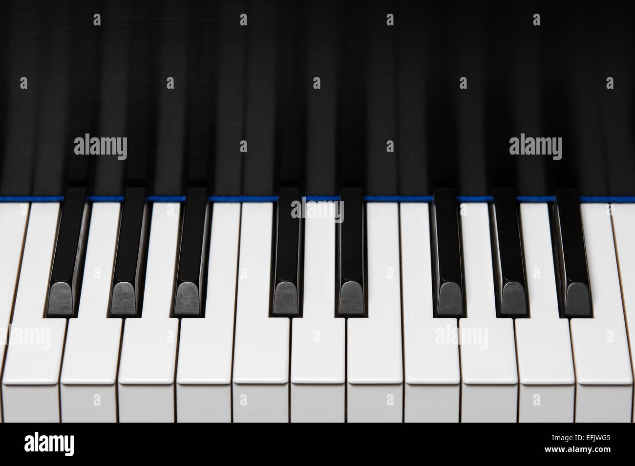 Section of piano keyboard showing one octave plus two extra keys on each end.  Key reflection in backboard.  Copy - Stock Image
